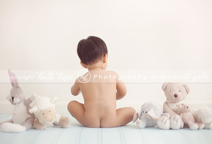 Stuffed animals surrounding 9 month old boy