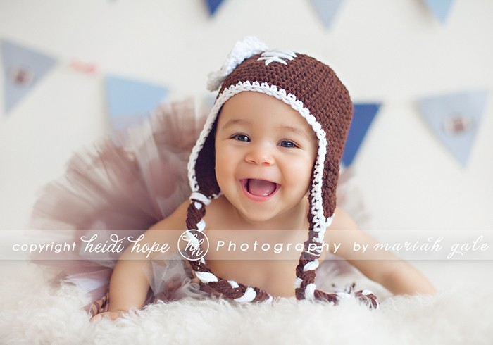 Smiling 7 month old girl in football hat