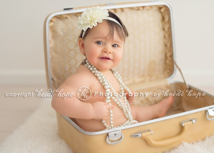Smiling one year old girl in suitcase wearing pearls