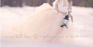 girl in bridal gown holding lantern in the snow