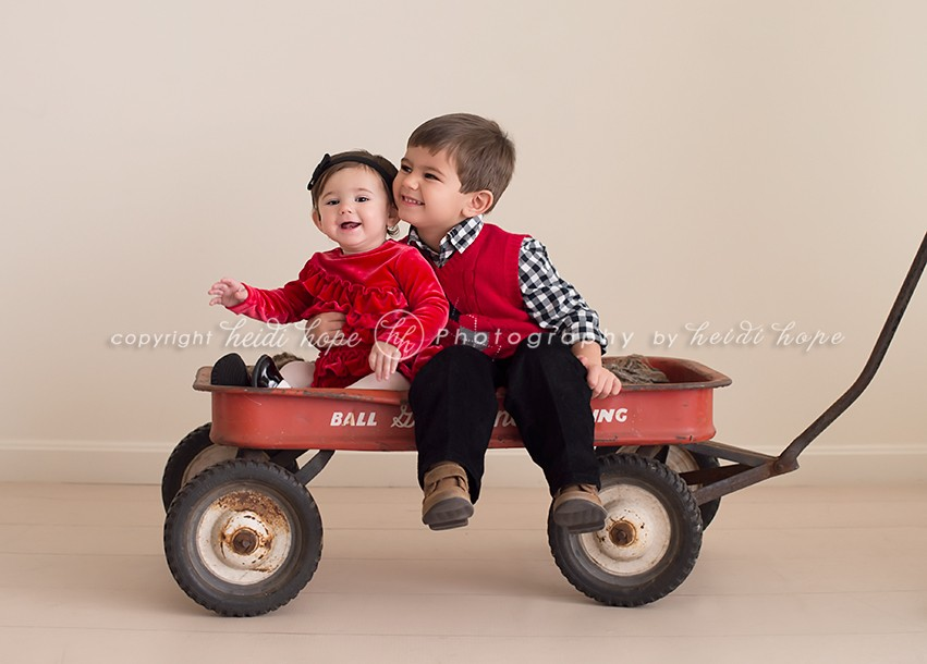 Brother and Sister sitting in wagon wearing holiday red - Heidi Hope Shoot