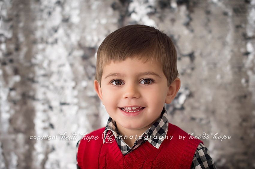 Little boy in holiday sweater in front of sequin back drop