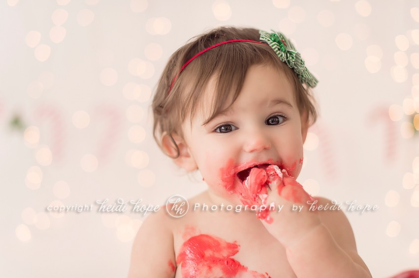 Up close little girl eating red cake from holiday cake smash - Heidi Hope