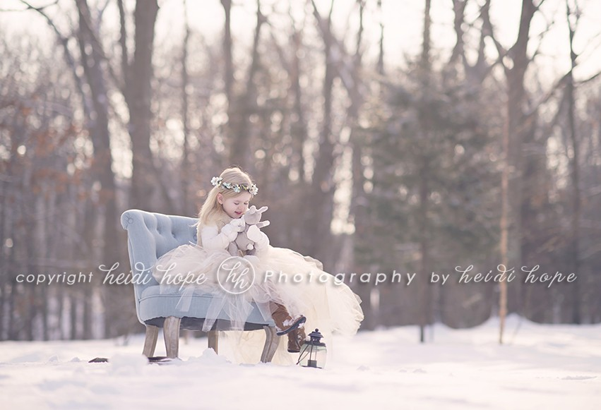Girl sitting on blue chair in snowy woods with a bunny
