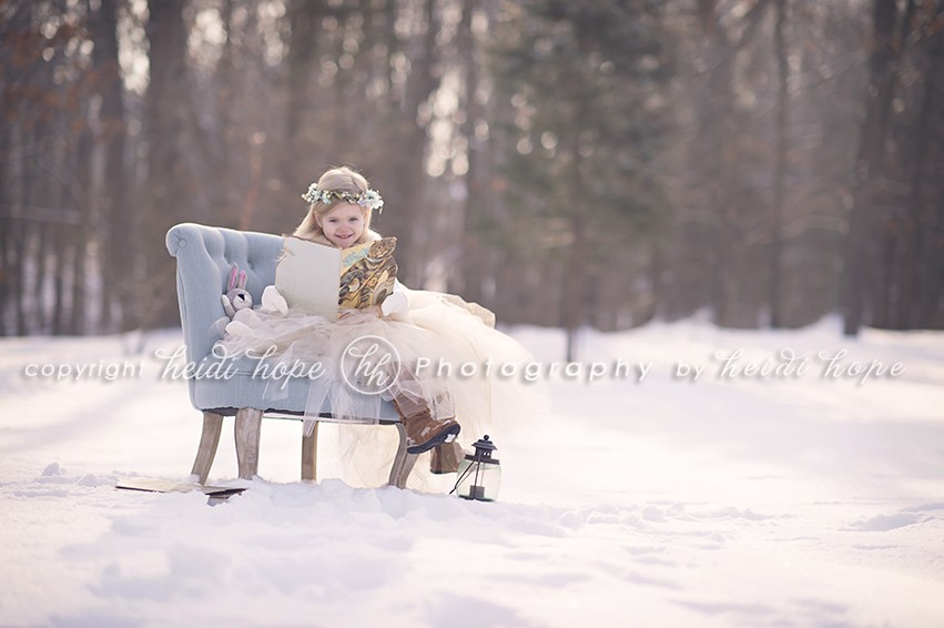 Girl sitting in blue chair in the snow reading a book