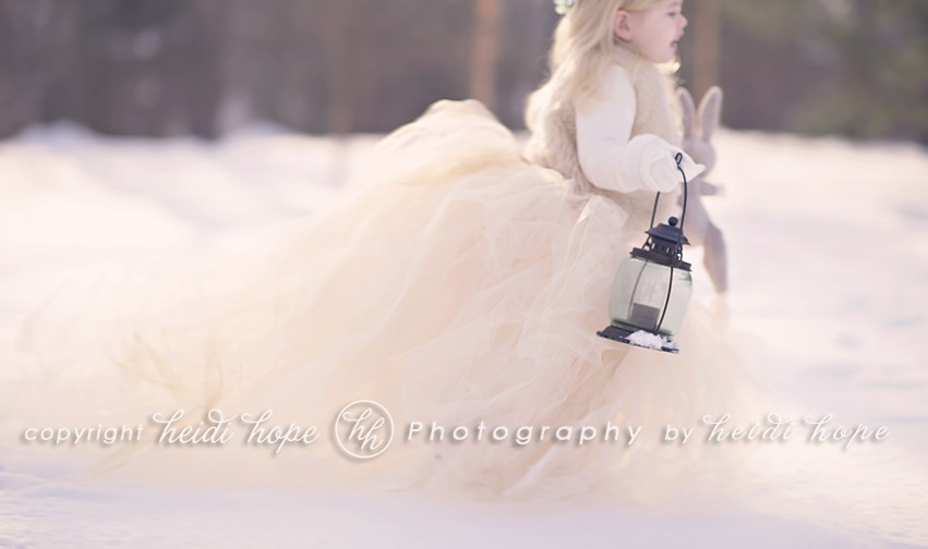 Girl in large tutu running through snowy woods with lantern