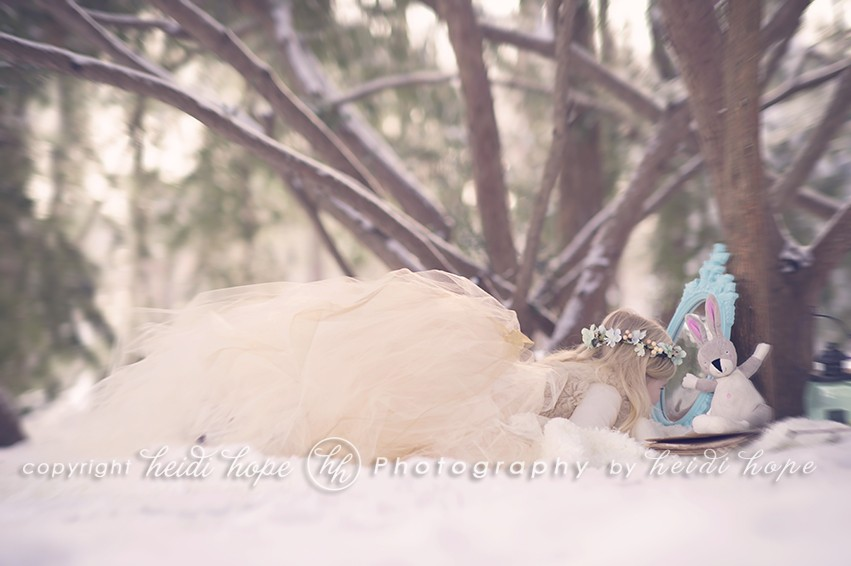 Snowy wood scene with girl in large tutu looking into a mirror