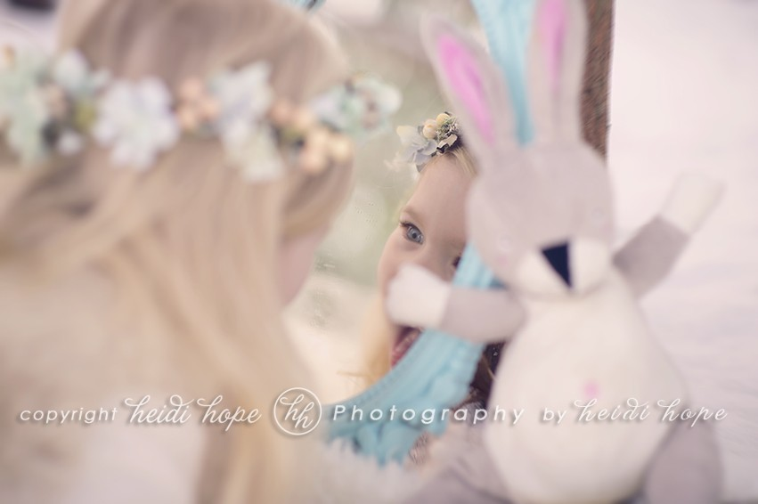 Snowy forest with girl looking at herself in blue mirror with bunny friend