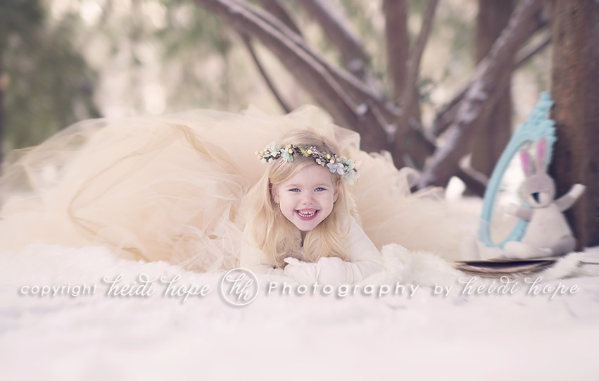Smiling Girl laying in snow with large tutu and bunny with mirror