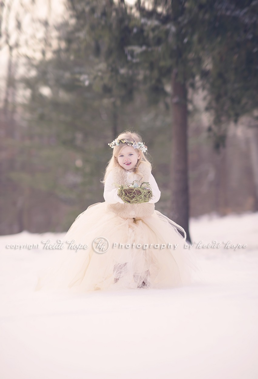 Girl in snowy woods in large tutu holding egg nest