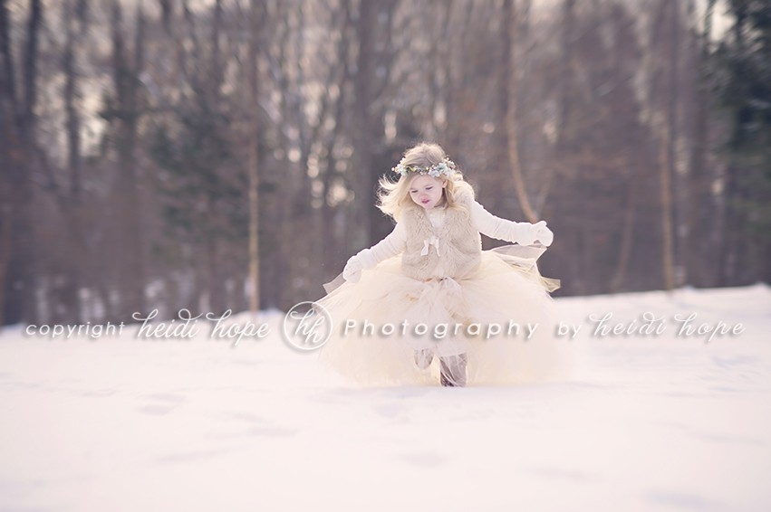 Girl running in the snowy woods in large tutu with headband