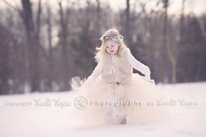 Girl looking down in snow in large tutu in the woods