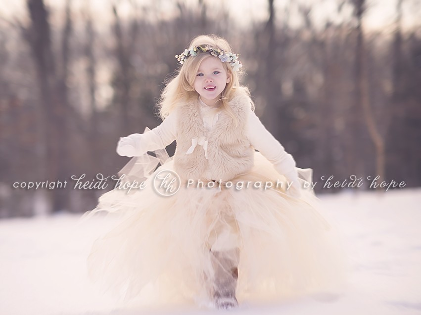 Girl running toward camera in a tutu in the snow