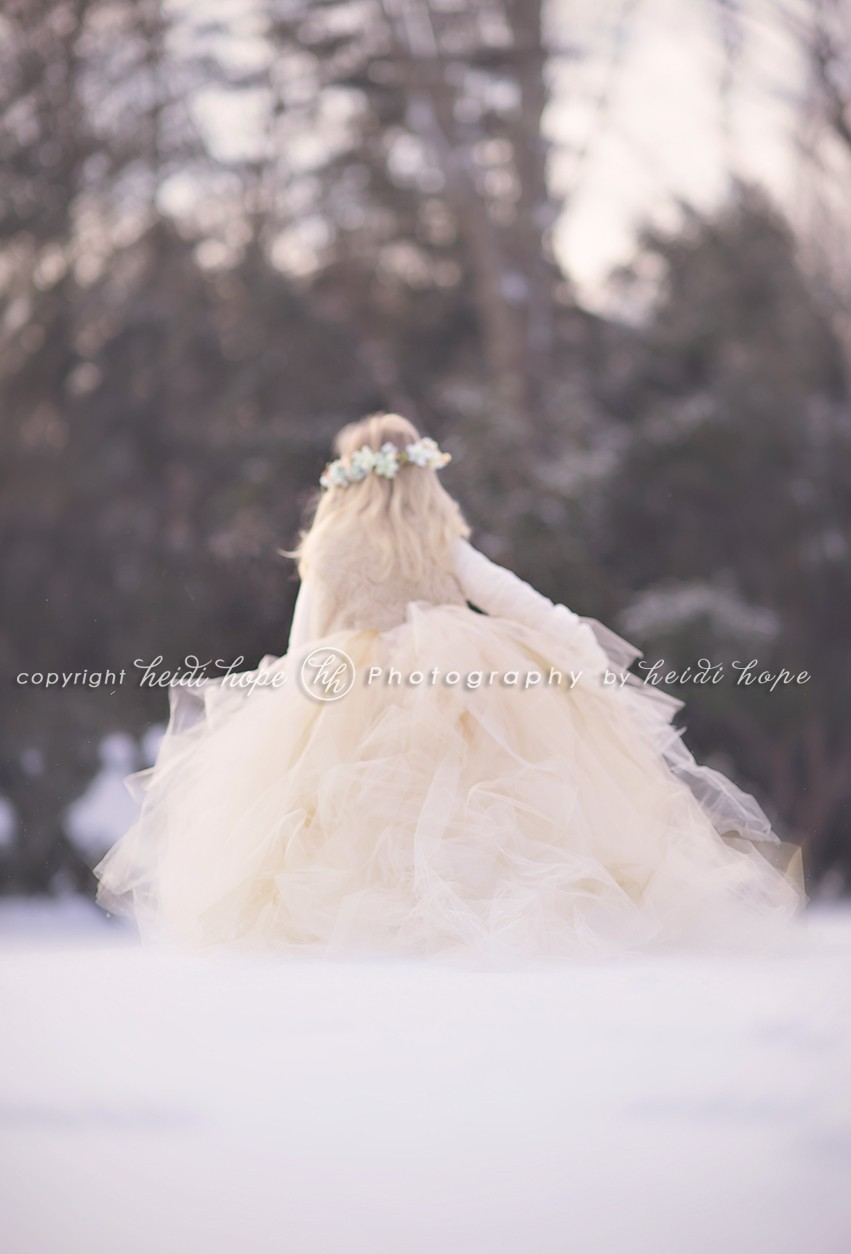 Girl running away in snow with a big tutu