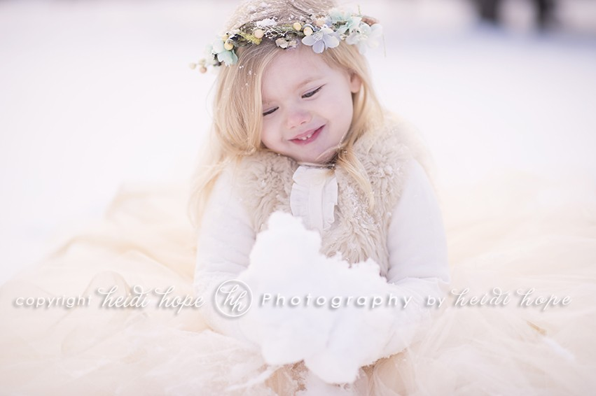 Girl with blue flowered headband holding snow