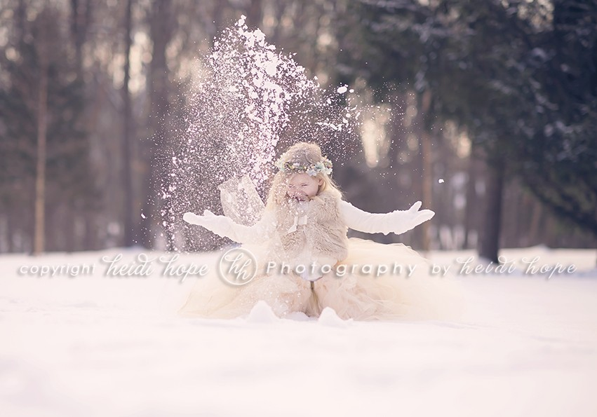Girl throwing snow up in the air in tutu