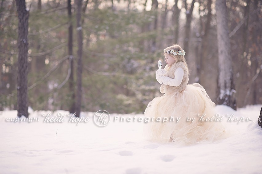 Girl in snow with tutu playing with a magnifying glass