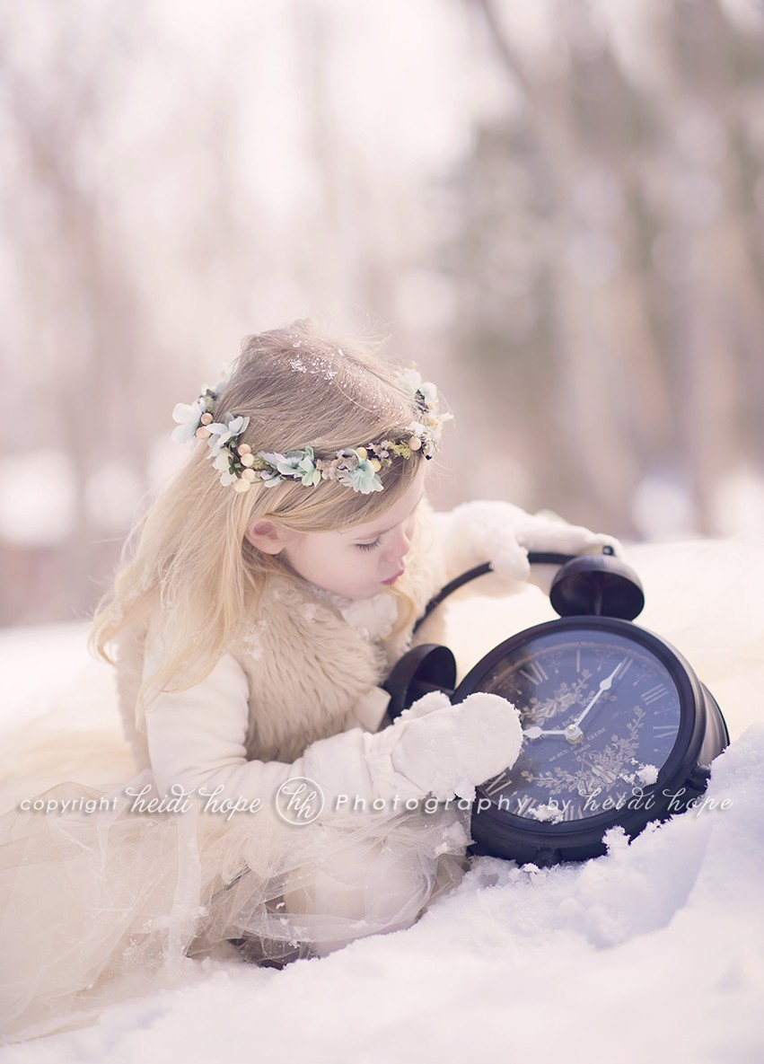 Girl with headband looking at a clock in the snow