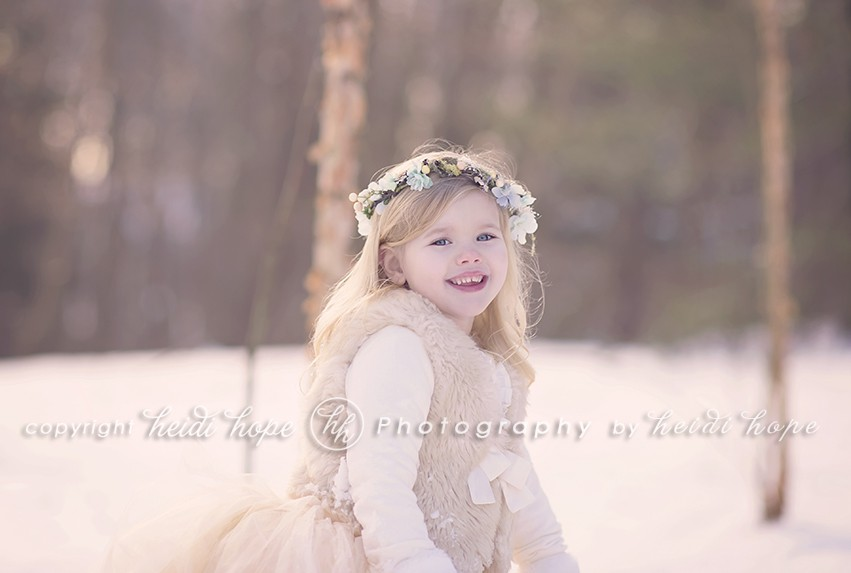 Smiling girl with blue flowered headband in snow