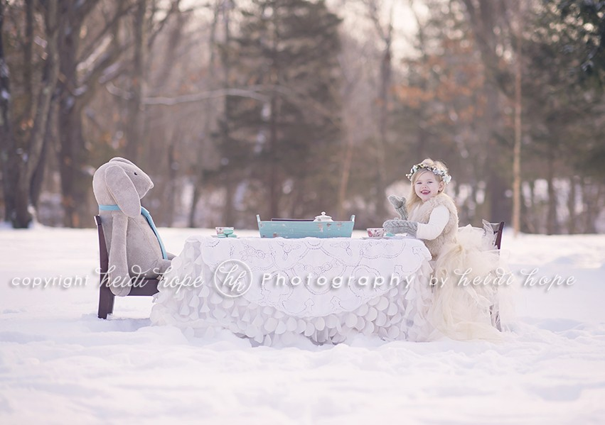 Girl waving sitting at snowy tea party